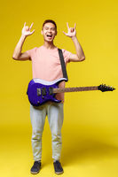 Full length Handsome young musician playing the guitar and singing, isolated on yellow background