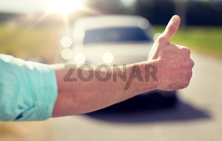 man hitchhiking and stopping car with thumbs up