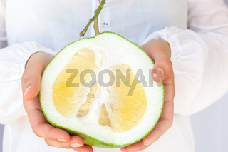 Woman holding healthy pomelo fruit.