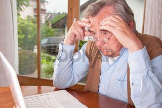 Frustrierter Senior sitzt vor Laptop