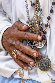 Detail of hands holding religious symbols