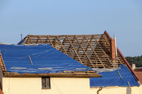 The tarp covers the roof of the old house in the reconstruction. The protective tarpaulin on the roof is incomplete.