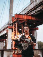 Guy reads a burning newspaper, in the background a bridge