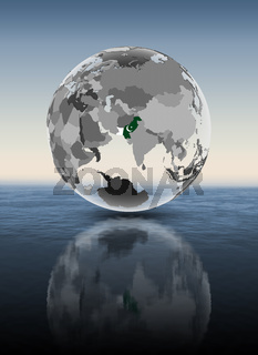 Pakistan on translucent globe above water