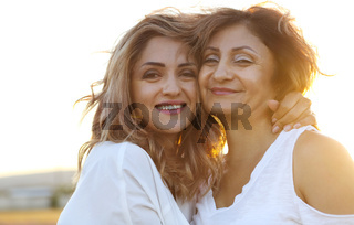 Middle age woman with her adult daughter in sunset light