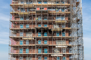 Construction site new apartment building with scaffolding and mason workers