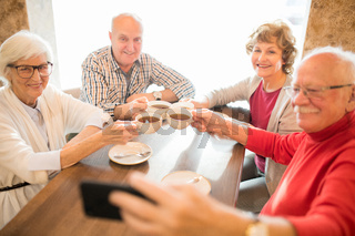 Cheerful seniors photographing together while drinking tea