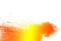 Yellow orange color powder splatter on white background. Color particles splash
