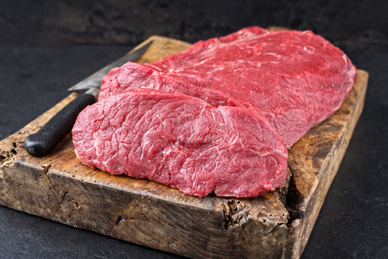 Raw roast beef offered as closeup on an old rustic wooden cutting board
