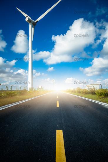 Wind turbines on landscape along empty road against sky