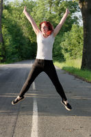 Sporty young redhead woman jumping for joy