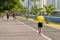 people running in public park with city skyline in background, Panama city -