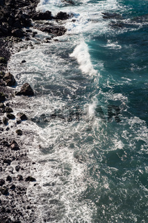 beautiful view on ocean water and black lava sand