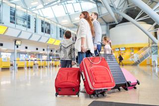Familie und Kinder mit vielen Koffern im Flughafen