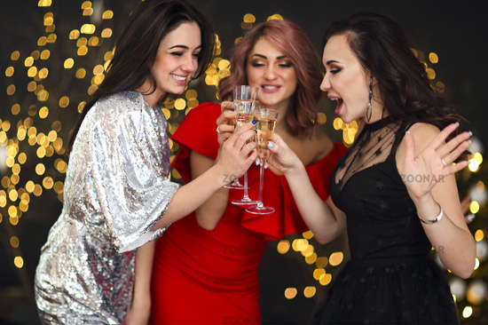 Smiling women in evening dresses with glasses of champagne over lights background