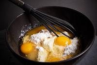 Ruehrschuessel und Schneebesen mit Eiern, Mehl und Zucker