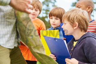 Kinder mit Klemmbrett spielen Schatzsuche