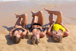 Three european girls sunbathing on beach