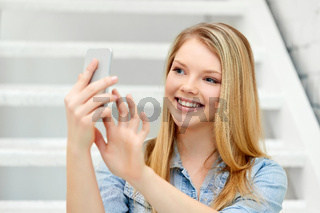 teenage girl taking selfie by smartphone on stairs