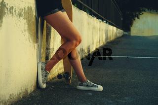 Elegant slim legs of female longboard skater in skate park a lot of copyspace.