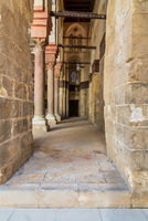 Passage at Sultan Qalawun Mosque with stone columns and colored stained glass windows, Cairo, Egypt