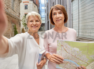 senior women with map and city guide taking selfie