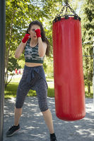 Attractive young woman in sportswear beats a punching bag