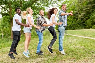 Gruppe beim Hüpfen auf einer Wiese