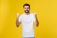 Happy young man with arms up isolated on a yellow background.