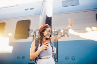 backpack traveler woman waving hand at train station platform summer holiday traveling concept. Female tourist greeting and enjoy on train, travel concept. Theme transportation and travel