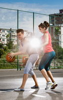 Young man and woman playing basketball on the playground