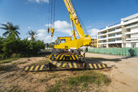 Yellow automobile crane with risen telescopic boom outdoors. Mobile construction crane on a constructin site. Crane machine stand by waiting for work under the construction building. Heavy industry.