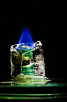 Blue flame melting down greenish icecube in front of black background