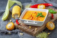 Delicious creamy corn soup with chili in a bowl.