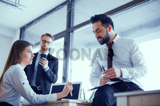 Beautiful business people are studying documents, talking and smiling while working in office
