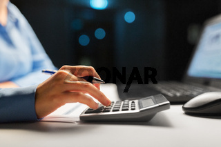 businesswoman with calculator at night office