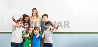 Schüler einer Klasse mit Lehrer halten Daumen hoch