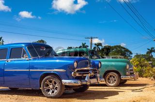 Blauer und grüner amerikanischer Oldtimer in der Seitenansicht im Landesinneren von Kuba - Serie Kuba Reportage