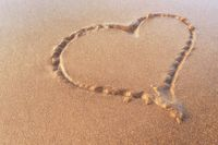 Heart drawn on the sand of the beach. Love concept.