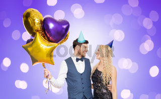 happy couple with party caps and balloons