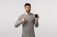 Friendly handsome and delighted bearded man in grey sweater recommend use application or like new messanger, shopping site, holding smartphone, show thumb-up in approval, like, smiling pleased