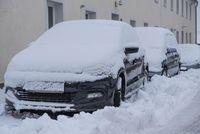 eingeschneites Auto - Wintereinbruch und Schneefahrbahn