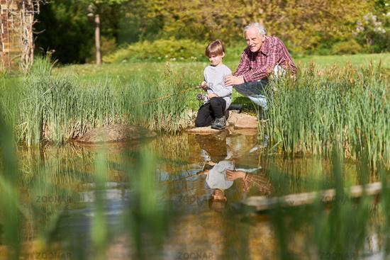 Großvater und Enkelsohn mit Angel beim Angeln