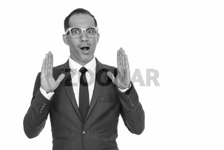 Mature handsome Persian businessman with eyeglasses looking shocked