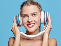 Young pretty happy woman in yellow dress listening to music in headphones