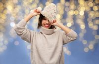 young woman in winter hat and sweater on christmas