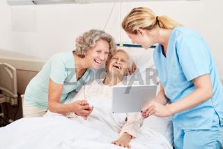 Pflegekraft zeigt Senior Frau einen Tablet PC