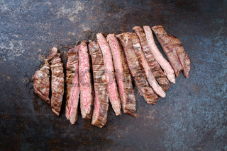 Barbecue dry aged wagyu flank steak sliced as top view on an old metal sheet with copy space
