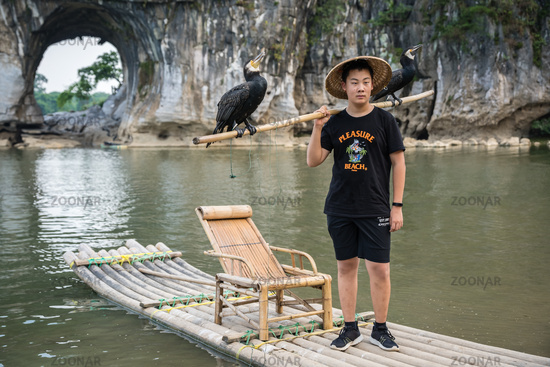 Man with cormorants in front of The Elephant Trunk Hill Arch