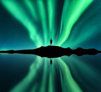 Aurora borealis, man and lake with sky reflection in water